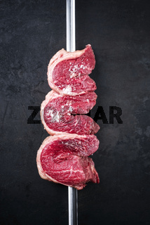 Raw dry aged wagyu picanha barbecue skewer from the cap of rump beef sliced and with salt offered as top view on an old rustic black board with copy space