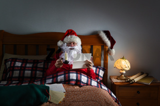 Santa Claus reading letters by candlelight in bed at his North Pole home.