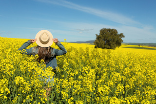 Female in denim jacket and shorts  in a field of flowering canola