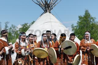 Group of people in clothing aborigine of Kamchatka stand on background at yaranga