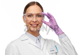 smiling female scientist in goggles and gloves