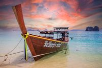 Amazing sunset over longtail boat on beach in Thailand