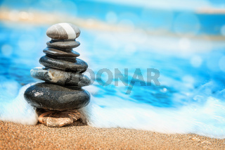 Stones pyramid on sand symbolizing zen