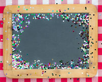 Vintage wooden blackboard with confetti
