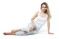Young pretty in jeans and shirt woman sitting on white studio  background