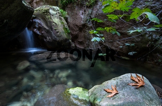 Idyllic calm lake with blue clean water and small waterfall flowing between the rocks.