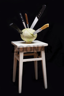 Knives stuck on a white cabbage put on a wooden stool