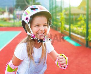 Little girl in roller skates on the playground