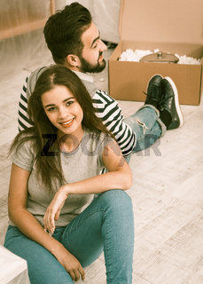 Happy man and woman sitting on the floor tired preparing to relocate to new apartment