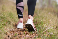 Rear close up view of female step on nature track. Young woman hiking in nature. Adventure, sport and exercise concept