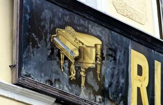 Alte schwarze Werbetafel mit goldenem Klavier