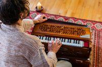Shamanic man playing harmonium indoors