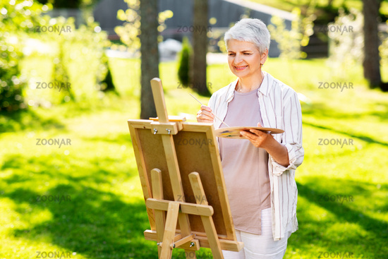 senior woman with easel painting outdoors