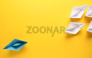 Teamwork business concept with paper boat on yellow background