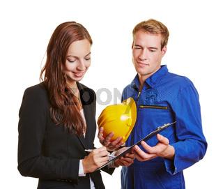 Geschäftsfrau mit Handwerker unterschreibt Auftrag