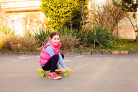 Smiling girl sitting on a skateboard in the city
