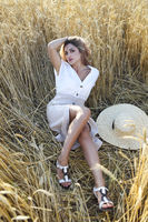 Beautiful young woman in light dress with straw hat on the wheat field