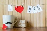 Fathers day greeting. Message with paper heart hanging with clothespins over wooden board. Happy Birthday