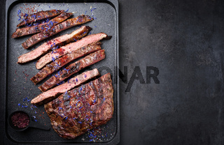 Modern design barbecue dry aged wagyu flank steak offered with herb and salt as top view on a modern design tray with copy space right