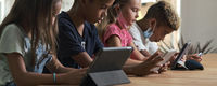 Four diverse kids wear facemasks sit at table use wireless gadgets
