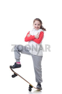 Cheerful little skateboarder posing with thumbs up