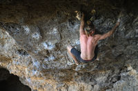 Young male climber bouldering a rock wall in a cave