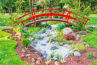 Red bridge above flowerbed in green park