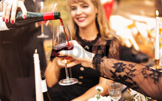 Crop women pouring wine during party