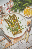 Roasted asparagus with parmesan cheese and parsley. Healthy spring food concept. View from above.