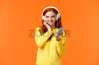 Sassy good-looking redhead female in yellow sweater, listen music white headphones, touch earphones and holding smartphone, listen music, enjoy good earbuds quality, smiling, orange background
