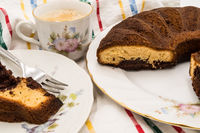 Slice of marbled cake on a plate with a cup of coffee