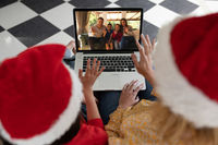 Rear view of woman and daughter in santa hats waving while having a videocall with family in santa h
