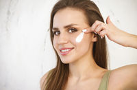 Young woman applying cream on face