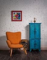 Vintage orange armchair, ornate scarf, and blue cupboard on grunge parquet floor and bricks wall