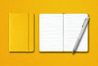 Yellow closed and open notebooks with a pen isolated on colorful background