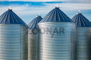 Large steel grain storage silos on farm