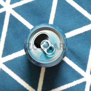Empty can on blue fabric background