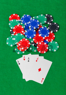 Casino chips and playing cards on green table