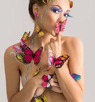 Bodyart. Pretty nude girl posing with butterflies