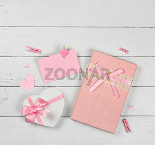 Pink gift boxes and paper note on white table