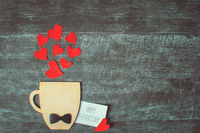 Fathers day concept. Decorative Cup with bow-tie and hearts on wooden background. Copyspace.