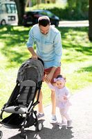father with child and stroller walking at park