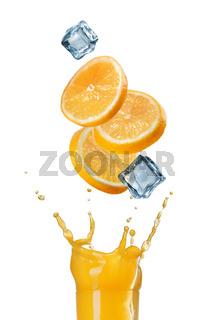 slices of orange falling into juice splash in glass isolated on white
