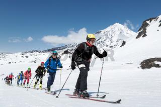 Ski mountaineering Championships: group ski mountaineer climb on skis on background volcano