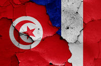 flags of Tunisia and France painted on cracked wall