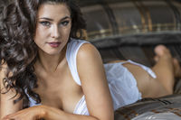 A Lovely Brunette Lingerie Model Poses In Lingerie In A Bedroom Environment