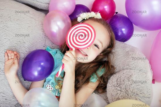 Playful curly girl hiding behind lollipop