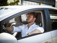 Handsome Man sleeping in a Car during daytime in a sunny day