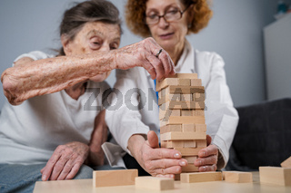 Senior woman practice skills, build wooden blocks, build tower and try not to let it fall, Jenga game. Old patient pull out block, place on top, support doctor during therapy dementia in house