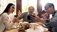 multigenerational asian family selfie and eating lunch together